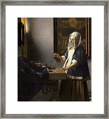 Woman Holding A Balance Framed Print by Jan Vermeer
