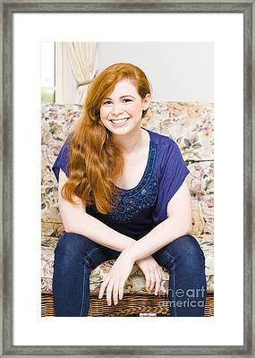 Woman Sitting On Lounge At Home Smiling Framed Print