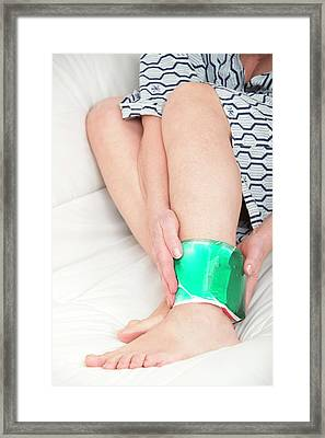 Woman With A Cold Compress On Ankle Framed Print by Lea Paterson