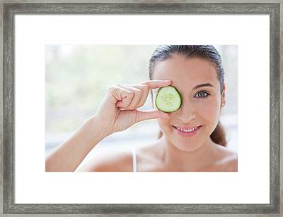Woman With Slice Of Cucumber Framed Print by Ian Hooton