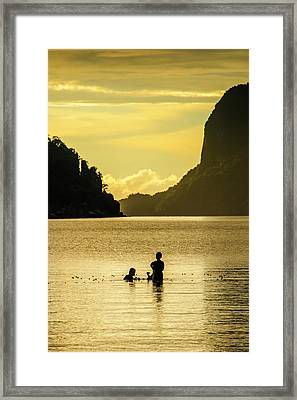 Young Boys Fishing At Sunset In The Bay Framed Print by Michael Runkel