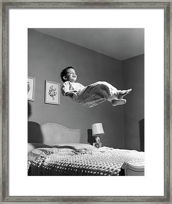 1950s Boy In Pajamas Elevated Above Bed Framed Print