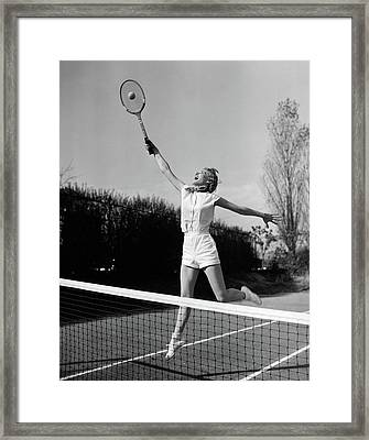 1950s Woman Jumping To Hit Tennis Ball Framed Print