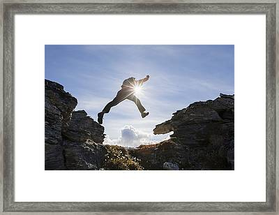 Backlit View Of Hiker Leaping Between Framed Print
