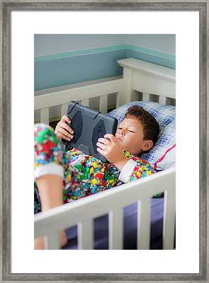 Boy In Bed Using A Digital Tablet Framed Print