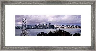 Bridge Across A Bay With City Skyline Framed Print