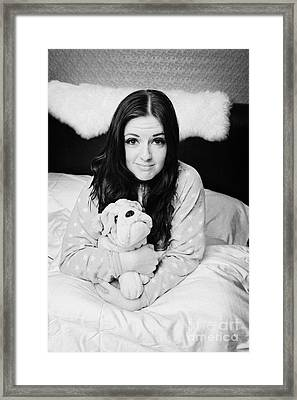 Early Twenties Woman Holding Cuddly Dog Soft Toy In Bed In A Bedroom Framed Print