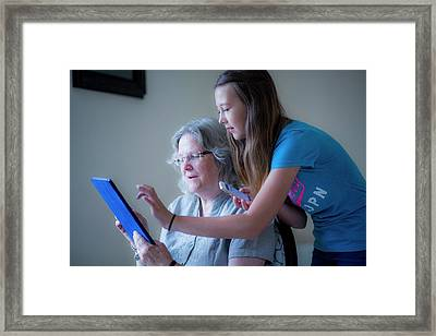 Girl And Grandmother Using Tablet Framed Print by Samuel Ashfield