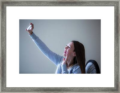 Girl Taking Selfie On Smartphone Framed Print by Samuel Ashfield