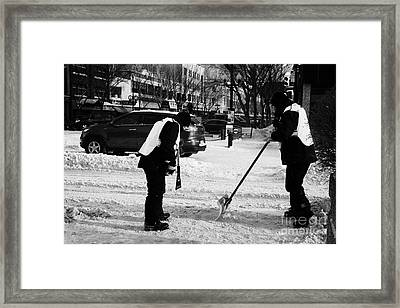 public workers clearing snow and ice off the sidewalks in downtown Saskatoon Saskatchewan Canada Framed Print by Joe Fox