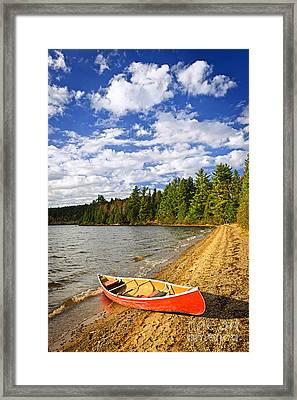 Red Canoe On Lake Shore Framed Print