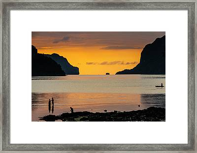 Silhouette Of Boys Fishing At Sunset Framed Print by Michael Runkel