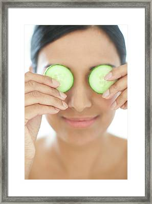 Woman Holding Slices Of Cucumber Framed Print by Ian Hooton