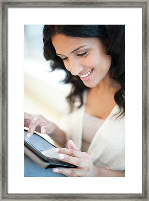 Woman Using Tablet Framed Print by Ian Hooton