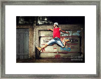 Young Man Jumping On Grunge Wall Framed Print by Michal Bednarek