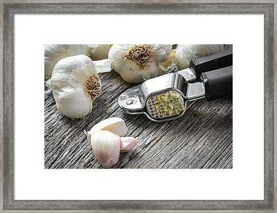 Garlic Press And Garlic Bulb Close Up On Rustic Wood Background Framed Print by Brandon Bourdages