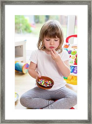 Girl Sitting On Floor With Bowl Of Sweets Framed Print by Aberration Films Ltd