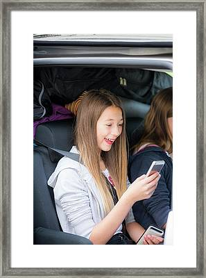 Girl Using Smartphone In Car Framed Print by Samuel Ashfield
