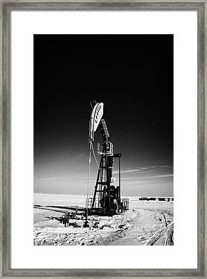 oil pumpjack in winter snow Forget Saskatchewan Framed Print by Joe Fox