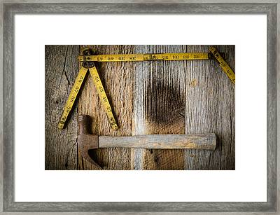 Old Tape Measure And Hammer For Construction On Rustic Wood Back Framed Print
