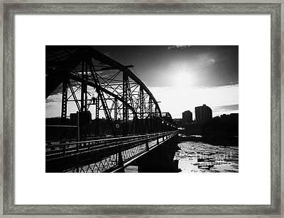 the old traffic bridge over the south saskatchewan river in winter flowing through downtown Saskatoo Framed Print by Joe Fox