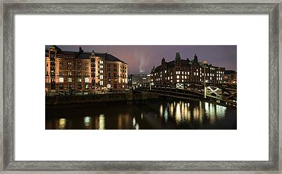 Buildings Lit Up At The Waterfront Framed Print
