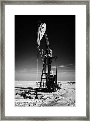 oil pumpjack in winter snow Forget Saskatchewan Canada Framed Print