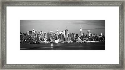Skyscrapers Lit Up At Night In A City Framed Print by Panoramic Images