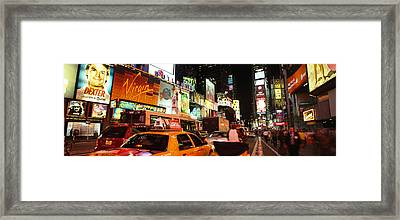 Buildings Lit Up At Night In A City Framed Print