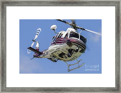 A Bell 412 Helicopter Flies Framed Print by Rob Edgcumbe
