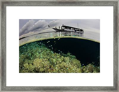 A Boat Sits Atop A Shallow Coral Reef Framed Print by Ethan Daniels