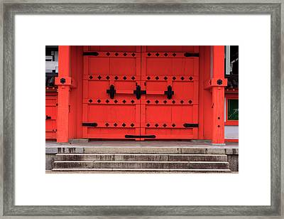 A Bright Red Door In The Grounds Framed Print by Paul Dymond