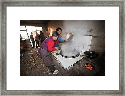 A Chinese Family Cooks On A Stove Framed Print by Ashley Cooper