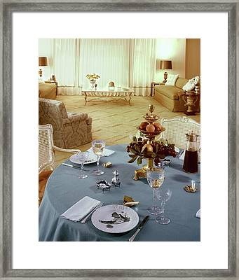 A Dining Room With A Blue Tablecloth And Ornate Framed Print