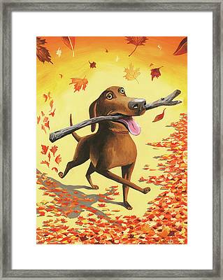 A Dog Carries A Stick Through Fall Leaves Framed Print