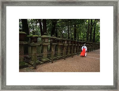 A Female Shrine Attendant Walks Framed Print by Paul Dymond