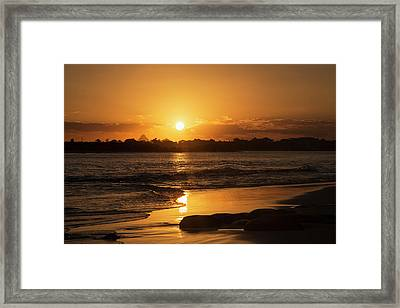 A Golden Sun Sets Over Silhouetted Framed Print by John Short
