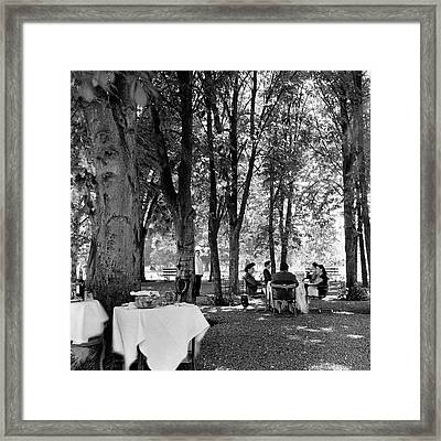 A Group Of People Eating Lunch Under Trees Framed Print by Luis Lemus