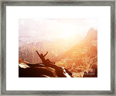 A Happy Man Sitting On The Peak Of A Mountain With Hands Raised At Sunset Framed Print
