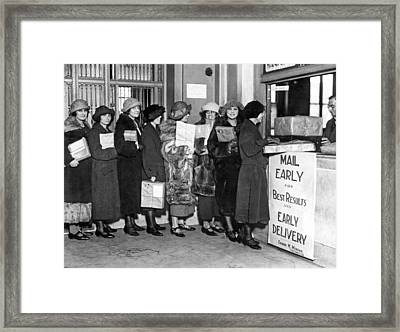 A Line Of Women At The Post Office Mailing Their Christmas Packa Framed Print by Underwood Archives