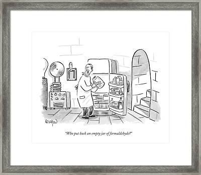 A Mad Scientist Removes A Jar From The Laboratory Framed Print by Robert Leighton