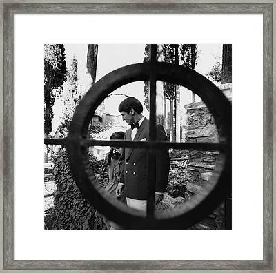 A Male And Female Model Behind A Gate Framed Print by Leonard Nones