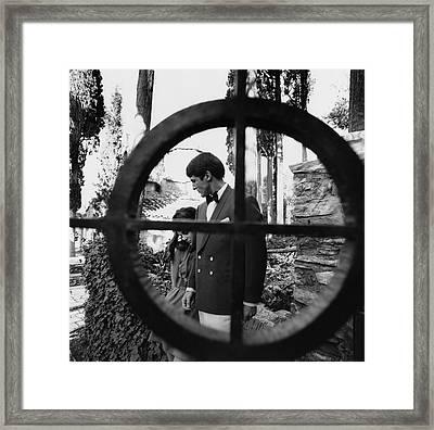 A Male And Female Model Behind A Gate Framed Print
