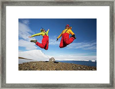 A Man And Woman Jumping For Joy Framed Print by Ashley Cooper