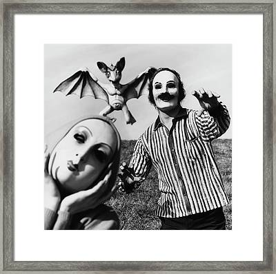 A Man And Woman Wearing Masks With A Bat Flying Framed Print by Chadwick Hall