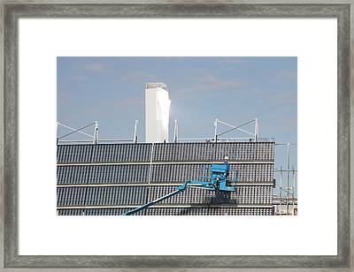 A Man Cleans Solar Panels Framed Print by Ashley Cooper