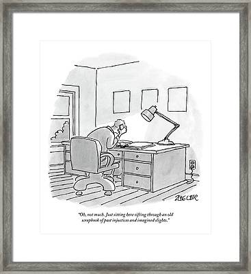 A Man Sits At A Desk Framed Print