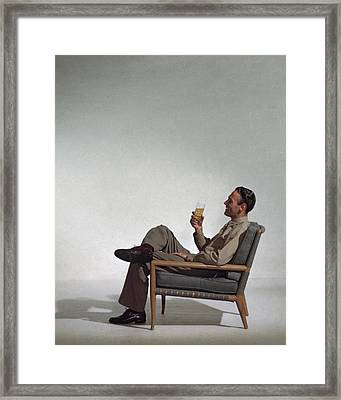 A Man Sitting In An Armchair With A Drink Framed Print by John Rawlings
