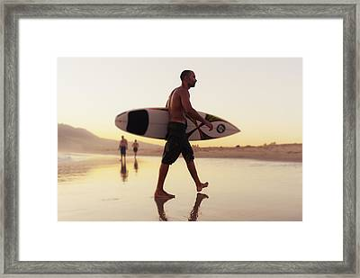 A Man Walking With His Surfboard On Framed Print