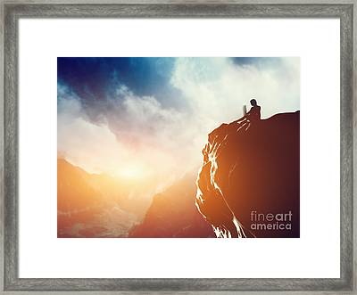 A Man Working On Laptop Sitting On The Peak Of A Mountain At Sunset Framed Print
